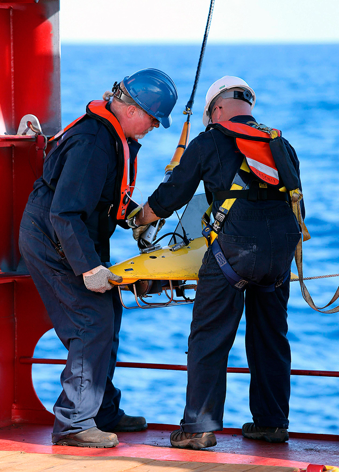 Phoenix International personnel, Mike Unzicker an0d Chris Minor deploy the towed pinger locator off the deck of the Australian Defence Vessel Ocean Shield in the southern Indian Ocean during the search for the flight data recorder and cockpit voice recorder of the missing Malaysian Airlines flight MH370 in this picture released by the Australian Defence Force yesterday. Photo: Reuters
