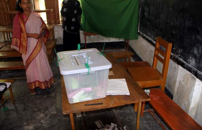 A woman is seen waiting beside a ballot box to cast her vote at Rajgur Government Primary School polling centre in Babuganj upazila of Barisal Saturday.  Seven chairman candidates in four districts boycott the third phase upazila elections alleging ouster of their agents and voters by ruling Awami League men. Photo: STAR