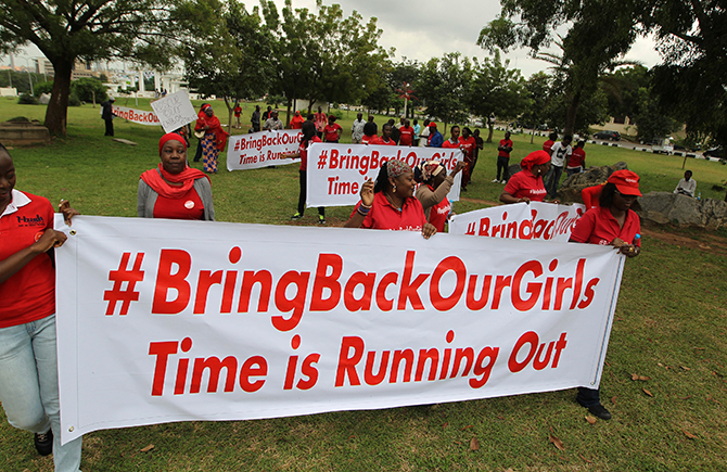 Demonstrators hold up banners during a rally that was held to mark the 120th day since the abduction of two hundred school girls by the Boko Haram, in Abuja August 12, 2014. Photo: Reuters