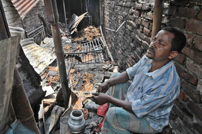 A man sits inside his burnt house at a Bihari camp in Mirpur area of the capital on Saturday. Photo: STAR