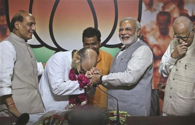 Indian Prime Minister Narendra Modi, second from right, greets newly appointed Bharatiya Janata party or BJP president Amit Shah, second from left, as outgoing party president Rajnath Singh, left, and BJP senior leader L.K.Advani watch, at the party's headquarters in New Delhi, India, Wednesday, July 9, 2014. Photo: AP