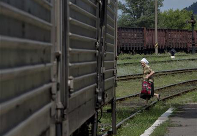 A woman looks at a refrigerated train loaded with the bodies of victims, in Torez, eastern Ukraine, 15 kilometers (9 miles) from the crash site of Malaysia Airlines Flight 17, Sunday. Photo: AP