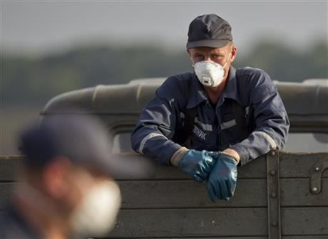 An emergency worker pauses in a truck loaded with bodies of the victims at the crash site of Malaysia Airlines Flight 17 near the village of Hrabove, eastern Ukraine, Saturday. Photo: AP