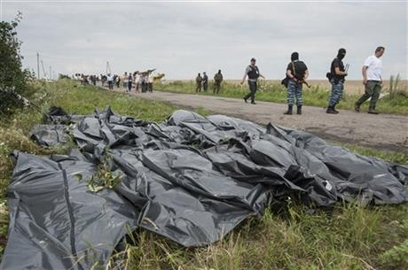 Pro-Russian fighters walk on a road with victims' bodies lying in bags by the side at the crash site of a Malaysia Airlines jet near the village of Hrabove, eastern Ukraine, Saturday. Photo: AP