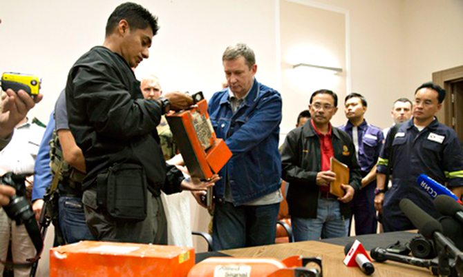 A Malaysian investigator, left, takes a black box from MH17 as it is handed over by a Donetsk People's Republic official on July 22. Photo: AP