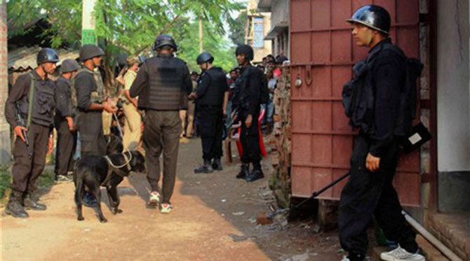 The law enforcers inspect the site where the explosion takes place in a house at Khagragarh village in Burdwan district of West Bengal. The photo is taken from The Indian Express.