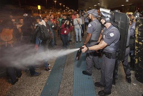 A police officer pepper sprays strikers and protesters during a clash with riot police in front of the Ana Rosa metro station, in an ongoing subway strike by operators, in Sao Paulo, Brazil on Monday. Photo: AP