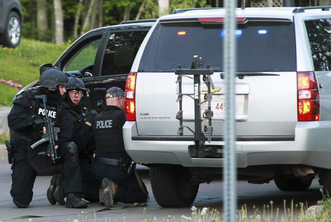 Emergency Response team members take cover behind vehicles in Moncton, New Brunswick June 4, 2014. Three police officers were shot dead and two more were wounded, police said as they conducted a manhunt for a man carrying a rifle and wearing camouflage clothes. Photo: Reuters