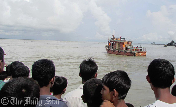 People gather on the bank of Meghna River at Gazipur point of Haimchar upazila in Chandpur as rescuers look for survivors of a capsized salt-laden trawler on Friday. Photo: Star