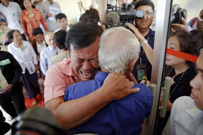 Soum Rithy (C), who lost his father and three siblings during the Khmer Rouge regime, breaks out in tears and hugs another survivor after the verdict was delivered in the trial of former Khmer Rouge head of state Khieu Samphan and former Khmer Rouge leader ''Brother Number Two'' Nuon Chea at the Extraordinary Chambers in the Courts of Cambodia (ECCC) on the outskirts Phnom Penh August 7, 2014. Photo: Reuters