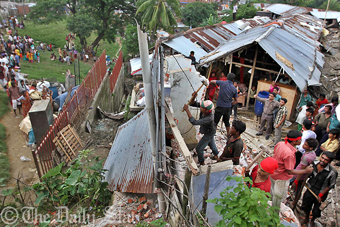 District administration with the help of law enforcers and members of fire service conduct an eviction drive against people living under the threat of landslides at Tankir Pahar in Lalkhan Bazar of Chittagong city. The hilly city faces heavy rainfall this monsoon. Photo: Star