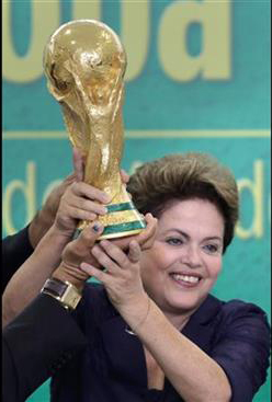 In this June 2, 2014 file photo, Brazil's President Dilma Rousseff holds up the 2014 World Cup trophy after it was officially presented to Rousseff by FIFA President Sepp Blatter, during a ceremony at the Planalto presidential palace, in Brasilia, Brazil. Photo: AP