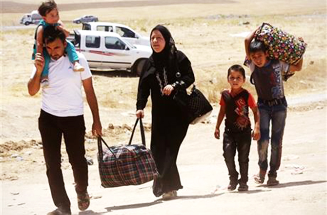 Iraqis who have fled the violence in their hometown of Mosul line arrive at Khazir refugee camp outside of Irbil, 217 miles (350 kilometers) north of Baghdad, Iraq on June 16, 2014. Photo: AP