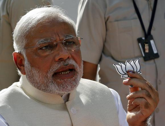 Hindu nationalist Narendra Modi, the prime ministerial candidate for India's main opposition Bharatiya Janata Party (BJP), holds a lotus cut-out after casting his vote at a polling station during the seventh phase of India's general election in the western Indian city of Ahmedabad April 30, 2014. Photo: Reuters