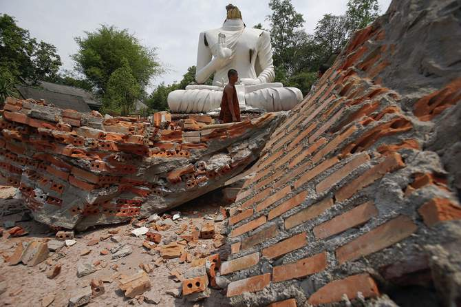 A Buddhist monk walks in front of a Buddha statue damaged in the earthquake at the Udomwaree temple in Chiang Rai, in northern Thailand May 6, 2014. Photo: Reuters