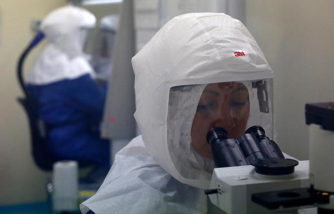A doctor uses a microscope to look at virus samples in a Biosafety Level III laboratory at the National Institute of Health in Lima, August 12, 2014. Photo: Reuters