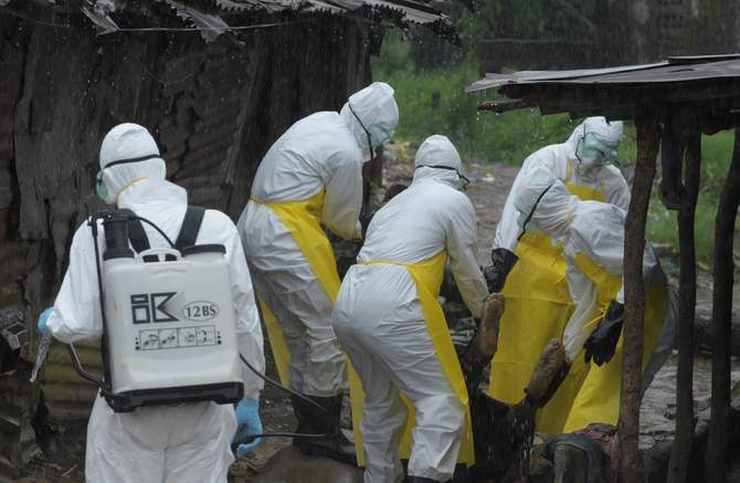 Health workers wearing protective clothing carry an abandoned dead body presenting with Ebola symptoms at Duwala market in Monrovia August 17, 2014. To try to control the Ebola epidemic spreading through West Africa, Liberia has quarantined remote villages at the epicentre of the virus, evoking the