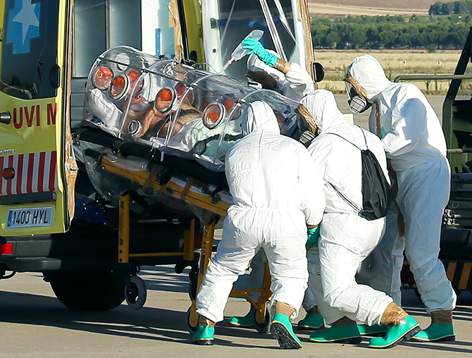 Health workers load Ebola patient, Spanish priest Miguel Pajares, into an ambulance on the tarmac of Torrejon airbase in Madrid, after he was repatriated from Liberia for treatment in Spain, August 7, 2014. Photo: Reuters
