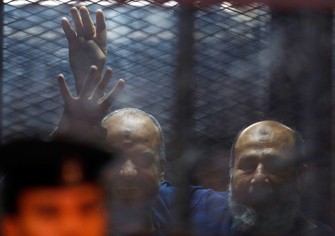 "Muslim Brotherhood's senior member Mohamed El-Beltagy and Islamist cleric Safwat Hegazis (R) gestures the four-fingered ""Rabaa"" hand symbol behind bars and glass panels from the defendant's cage at a courtroom in Cairo August 7, 2014. Photo: Reuters"