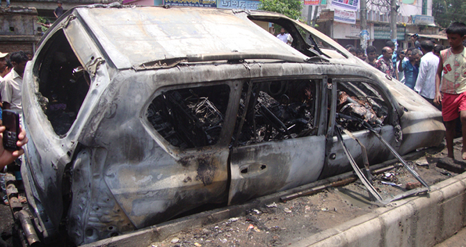 The burnt car of Phulgazi upazila chairman lies on a road in Academy area of Feni town after miscreants set fire to it on May 20, leaving the chairman dead on the spot. Photo: Star