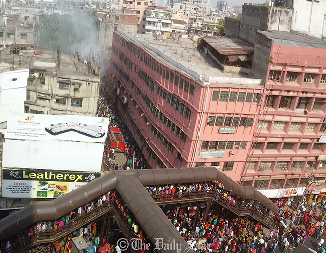 People gather in the area, just opposite to The Daily Star building at Farmgate, during the fire incident at a shop in the capital on Thursday. Photo: Star