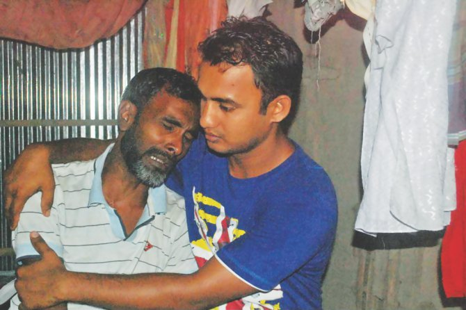 A relative consoles the brother of Elahi Hossain, 31, of the same district, as the two men along with Faruk Khan, 38, of Munshiganj were killed Monday in a construction site collapse in Malaysia where they went in hope of bettering their lives. Photo: Star
