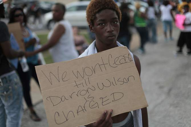 A demonstrator holds a sign during a protest against the shooting death of Michael Brown in Ferguson, Missouri August 18, 2014. Missouri Governor Jay Nixon lifted the curfew for the St. Louis suburb of Ferguson on Monday and began deploying National Guard troops to help quell days of rioting and protests spurred by the fatal shooting of the black unarmed teenager by a white policeman. Photo: Reuters