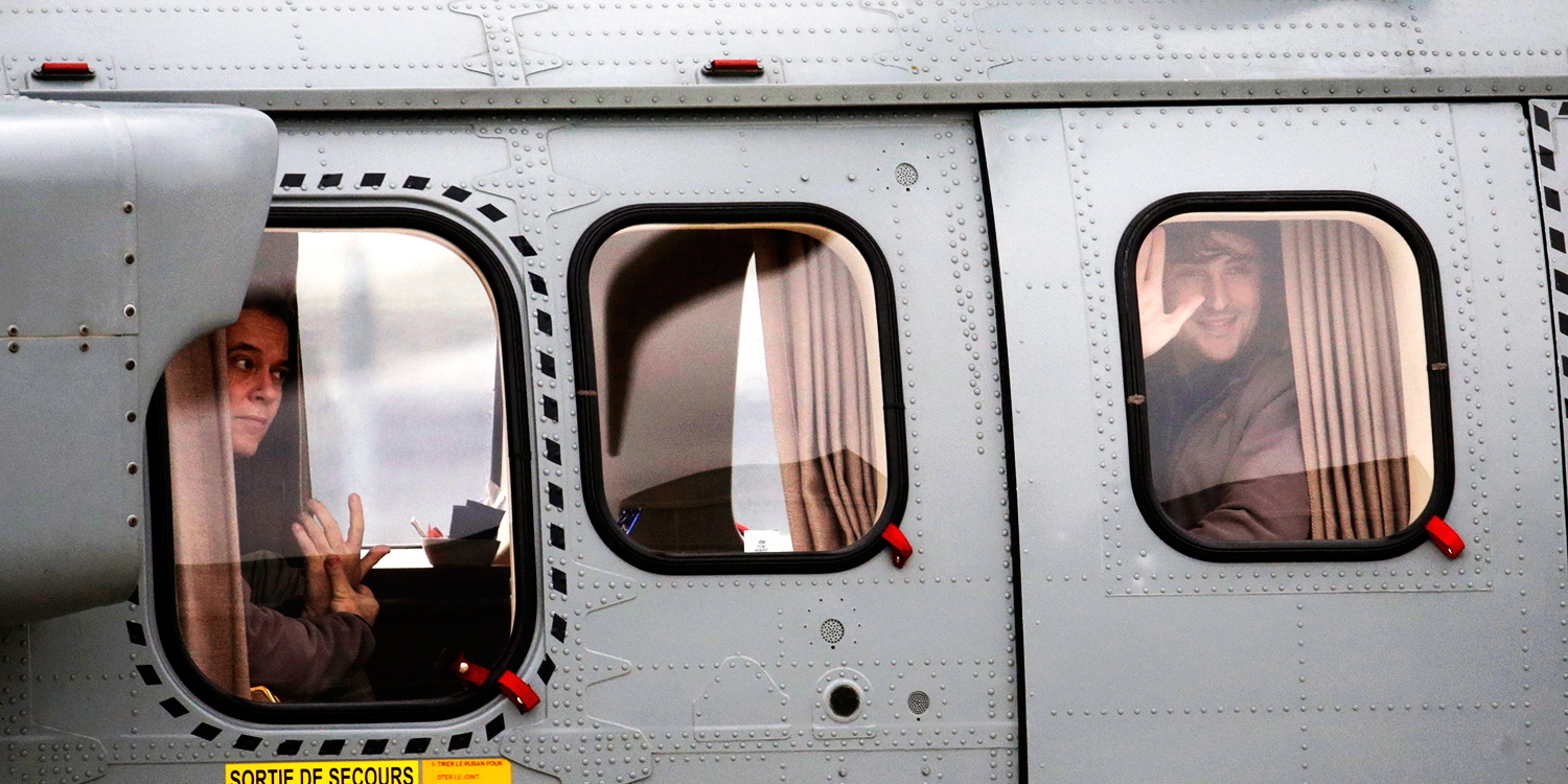 Former French hostages and journalists Didier Francois (L) and Edouard Elias (R), who waves, look toward awaiting media from inside their helicopter at their arrival to the military airbase in Villacoulbay, near Paris. Photo: Reuters