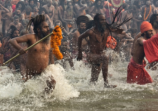 "This Reuters file photo from last year shows Hindu holy men take a dip during the first ""Shahi Snan"" (grand bath) at the ongoing ""Kumbh Mela""."