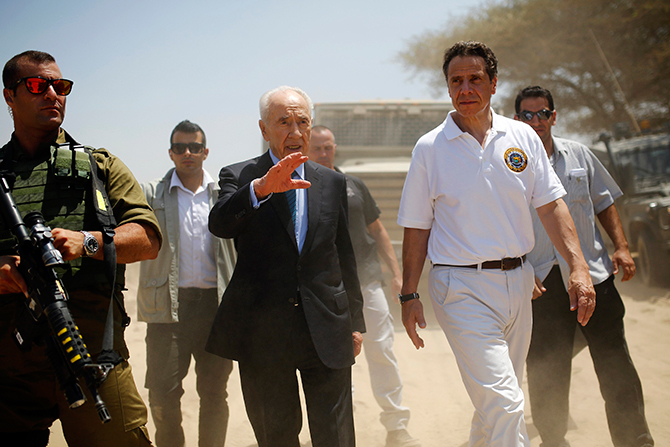 Former Israeli President Shimon Peres (C) and New York Governor Andrew Cuomo (R) walk together during a tour to see a tunnel exposed by the Israeli military on the Israeli side of the Israel-Gaza border August 14, 2014.  Photo: Reuters