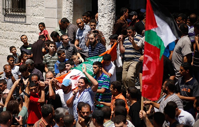 Mourners chant slogans during the funeral of the wife of Hamas's military leader, Mohammed Deif, his infant son Ali and other Palestinians whom medics said were killed in Israeli air strikes, in the northern Gaza Strip August 20, 2014. Photo: Reuters