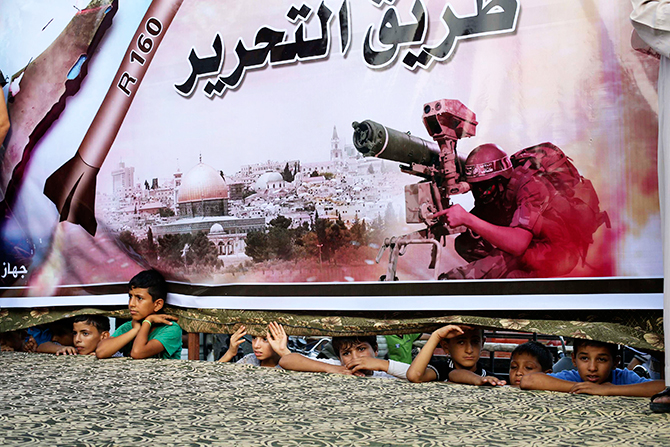 Palestinians watch through a large Hamas poster at a rally in support of the armed Palestinian factions, in Rafah in the southern Gaza Strip August 17, 2014.