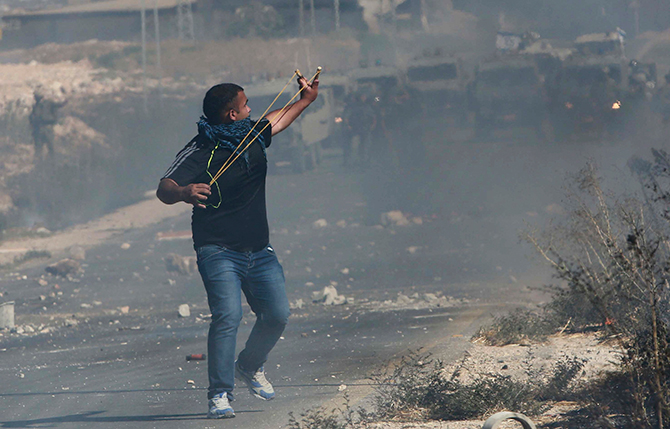A Palestinian protester uses a slingshot to hurl stones toward Israeli troops during clashes following a demonstration against the Israeli offensive in Gaza, at the Beit Fourik checkpoint near the West Bank of Nablus August 8, 2014. Photo: Reuters
