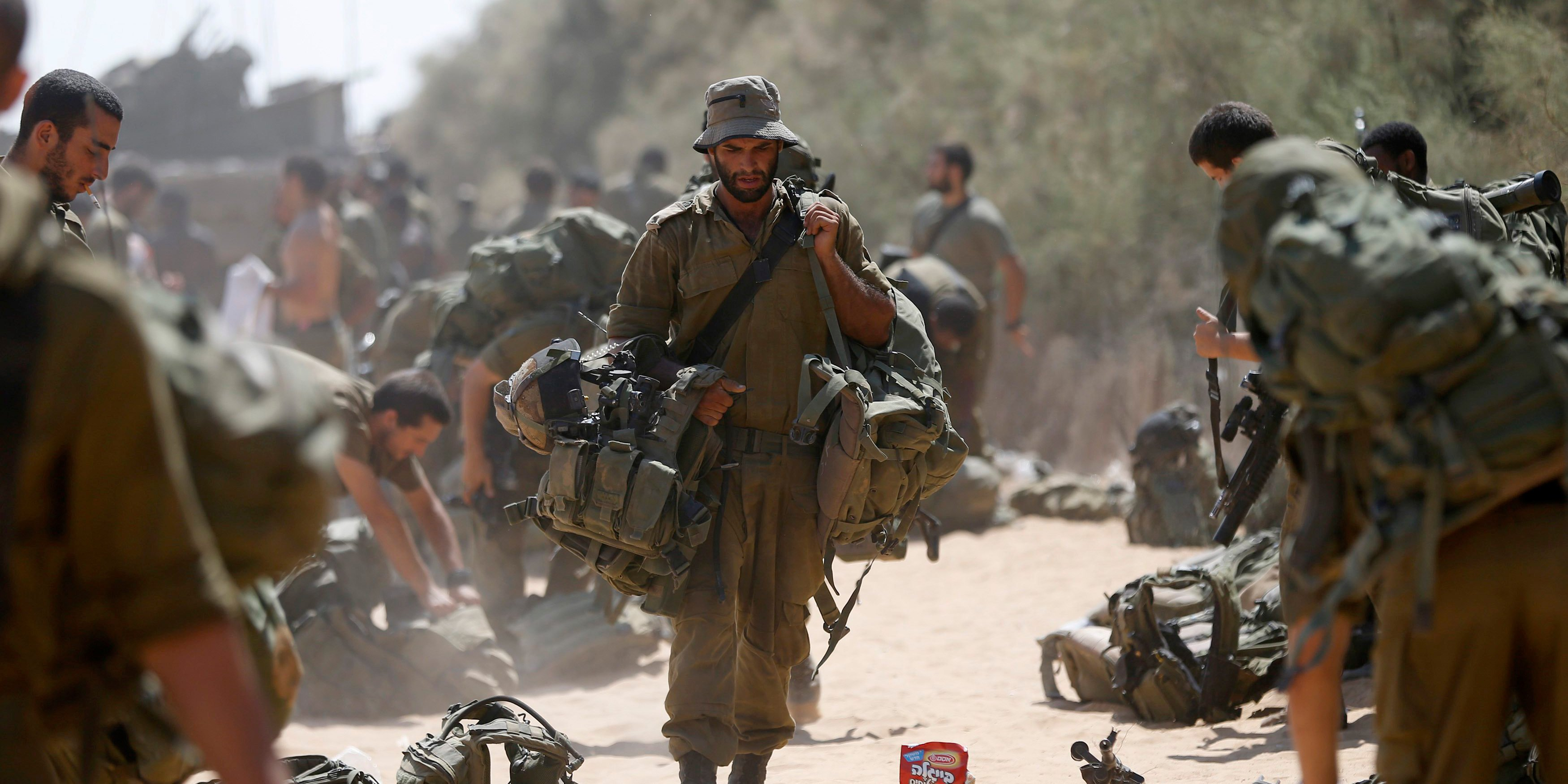 An Israeli soldier from the Givati brigade carries his gear after returning to Israel from Gaza August 4, 2014. Photo: Reuters
