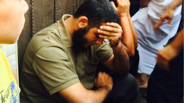The brother of Hamas fighter Nidal al-Malesh sitting in shock not long after his brother was killed in an Israeli missile strike. The photo is taken from BBC Online.