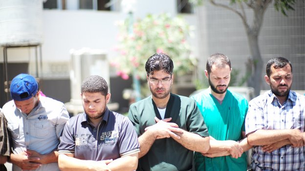 Medics at Shifa hospital pause during their work to make a collective prayer. The photo is taken from BBC Online.