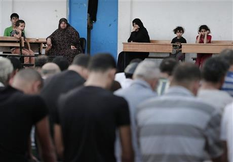 Palestinians displaced people watch as men pray in the courtyard of a U.N. school in Gaza City, Monday. Photo: AP