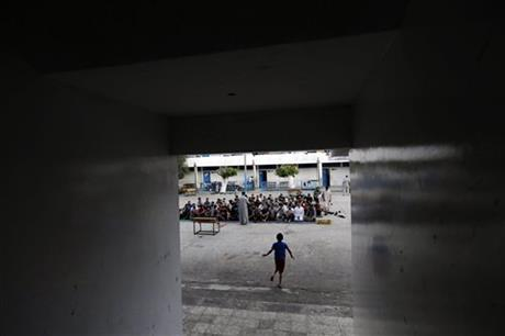 Palestinians listen to a sermon as they pray in the courtyard of a U.N. school in Gaza City, Monday. Photo: AP