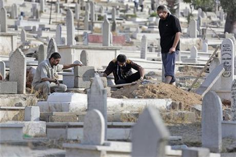 Relatives pause as they prepare the grave for their loved one, who died of natural causes, at a cemetery in Gaza City, in the northern Gaza Strip, Monday, July 28. Photo: AP