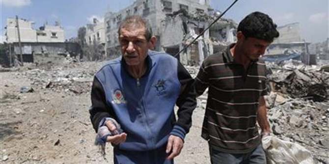 In this Sunday, July 20, 2014 photo a Palestinian man is helped to flee Gaza City's Shijaiyah neighborhood, after an Israeli strike in the area. Disagreement over whether to lift the Gaza blockade is a key stumbling block to ending more than two weeks of fighting between the Islamic militant Hamas and Israel. Some in Gaza say they would rather endure more fighting than return to life under the blockade. Photo: AP