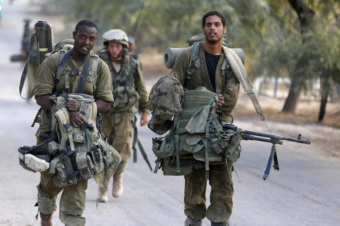 An Israeli soldier from the Nahal Brigade carry equipment after returning to Israel from Gaza August 5, 2014. Israel pulled its ground forces out of the Gaza Strip on Tuesday and started a 72-hour ceasefire with Hamas mediated by Egypt as a first step towards negotiations on a more enduring end to the month-old war. Photo: Reuters