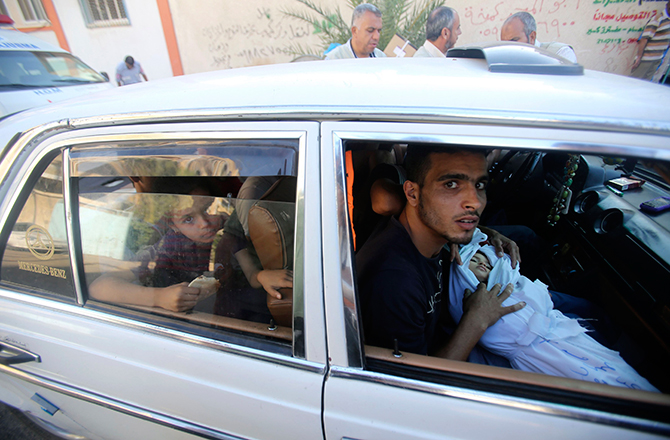 A relative sits in a car as he carries the body of two-and-a-half-year-old Palestinian girl Raghad Massoud, whom medics said was killed in an Israeli air strike, before her burial in Rafah in the southern Gaza Strip August 4, 2014. Israel said it would unilaterally hold fire in most of the Gaza Strip on Monday to facilitate the entry of humanitarian aid and allow some of the hundreds of thousands of Palestinians displaced by an almost four-week-old war to go home. Photo: Reuters