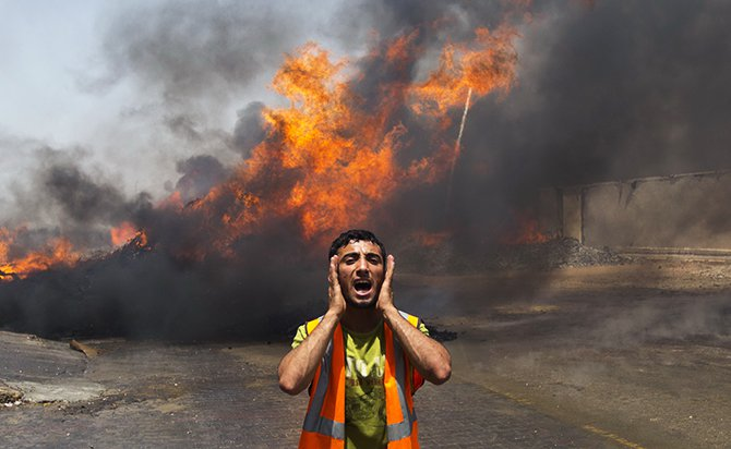Palestinian firefighters try to extinguish fire at UN storehouse after an Israeli military strike in an area west of Gaza City on July 12, 2014. Photo: Getty Images