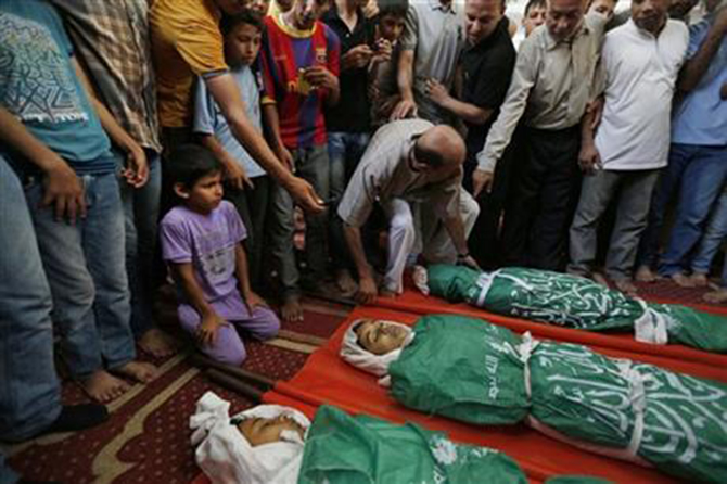 Palestinian mourners gather around the bodies of three siblings of the Abu Musallam family, during their funeral in Beit Lahiya, northern Gaza Strip, Friday. Photo: AP