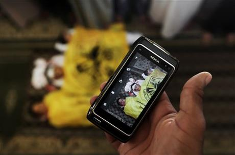 A man takes a photo with his mobile phone of the lifeless bodies of Qasim Alwan, 4, Imad Alwan, 6, and Rizk Hayek, 1, who were killed Friday by an Israeli tank shell, during their funeral in Gaza City, Saturday, July 19. Photo: AP