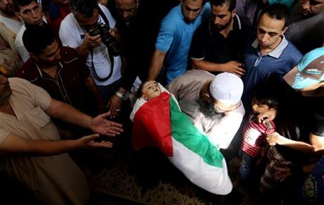 Palestinian mourners gather around the lifeless body of one year-old Rizk Hayek, who was killed Friday by an Israeli tank shell, during his funeral in Gaza City, Saturday. Photo: AP