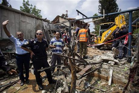 In this Tuesday, July 22, 2014, file photo, Israeli police officers secure a destroyed house that was hit by a rocket fired by Palestinians militants from Gaza, in Yahud, a Tel Aviv suburb near the airport, central Israel. Photo: AP