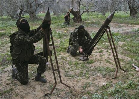 In this Dec. 20, 2008, file photo, masked Palestinian militants from Islamic Jihad place homemade rockets before later firing them into Israel on the outskirts of Gaza City. Photo: AP