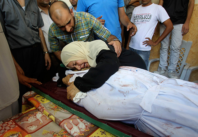 The mother-in-law of Palestinian translator Ali Shehda Abu Afash, whom medics said was killed when unexploded munitions blew up, mourns over his body during his funeral in Gaza City August 13, 2014. Photo: Reuters