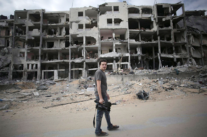 Associated Press video journalist Simone Camilli walks against a backdrop of destroyed buildings in Beit Lahiya in the Gaza Strip August 11, 2014. Italian journalist Camilli, three Palestinian bomb disposal experts and two other people were killed in Gaza on Wednesday when unexploded munitions blew up, medical officials and police said. Photo: Reuters